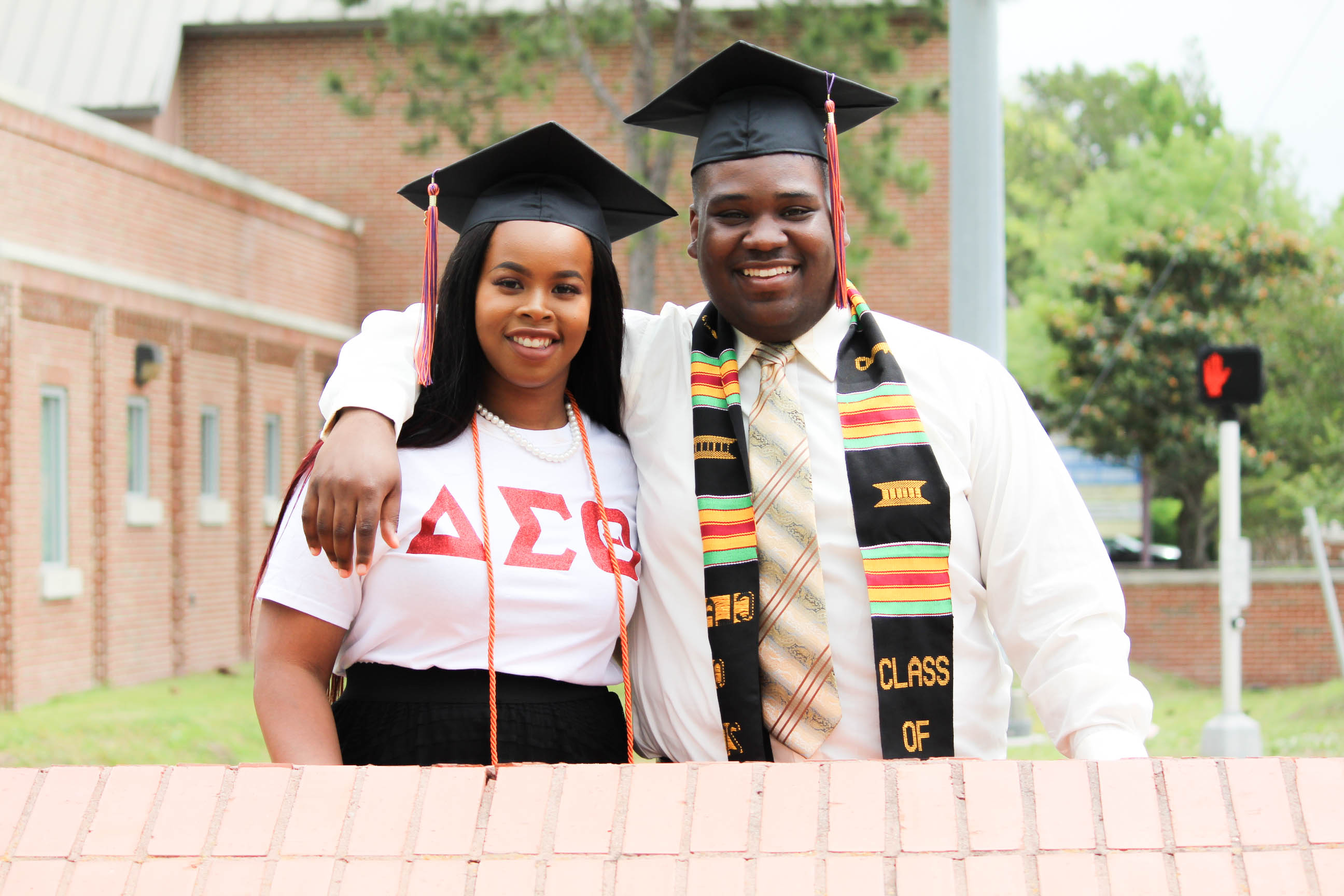 Female and Male student (left and right) smiling wearing graduation attire